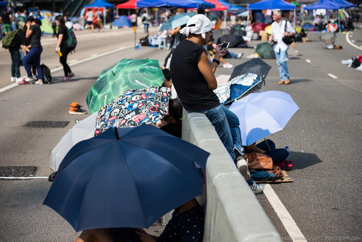 Протестующие прячутся под зонтами от солнца