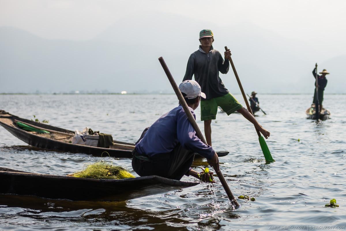 Рыбак толкает весло ногой стоя на лодке
