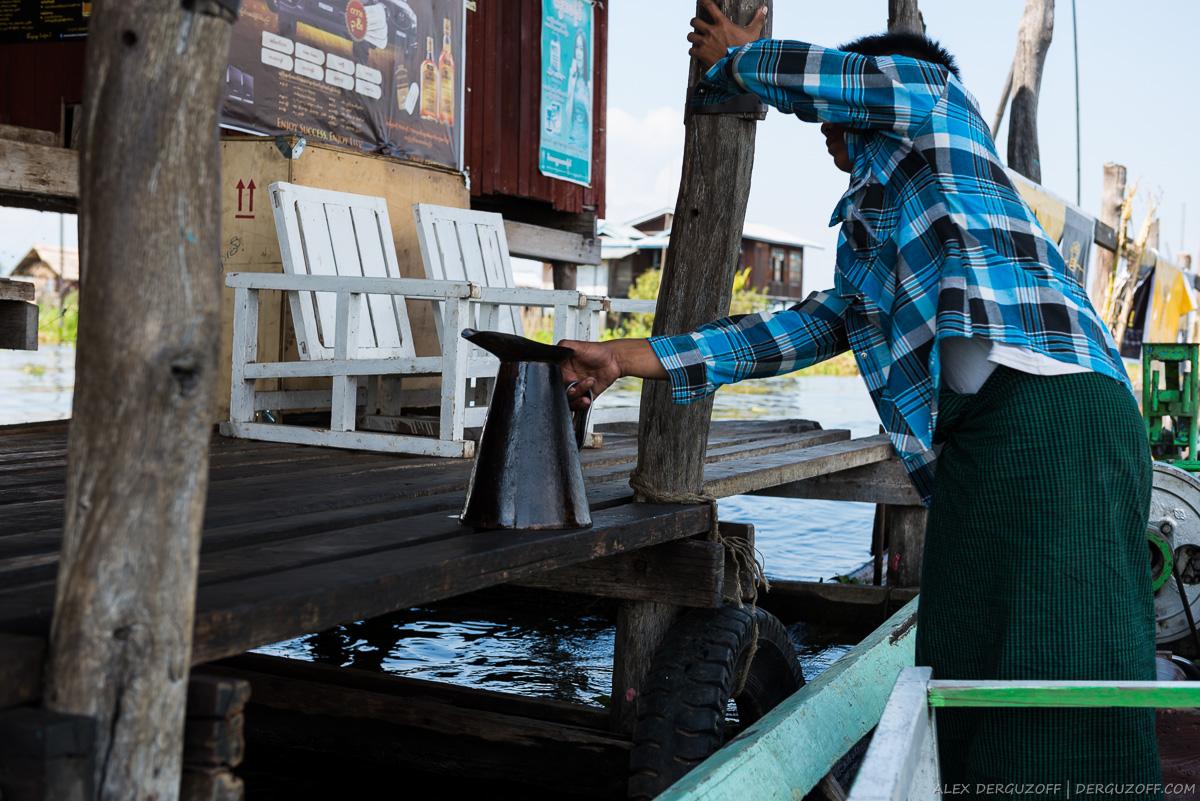 Водитель лодки берет канистру с горючим