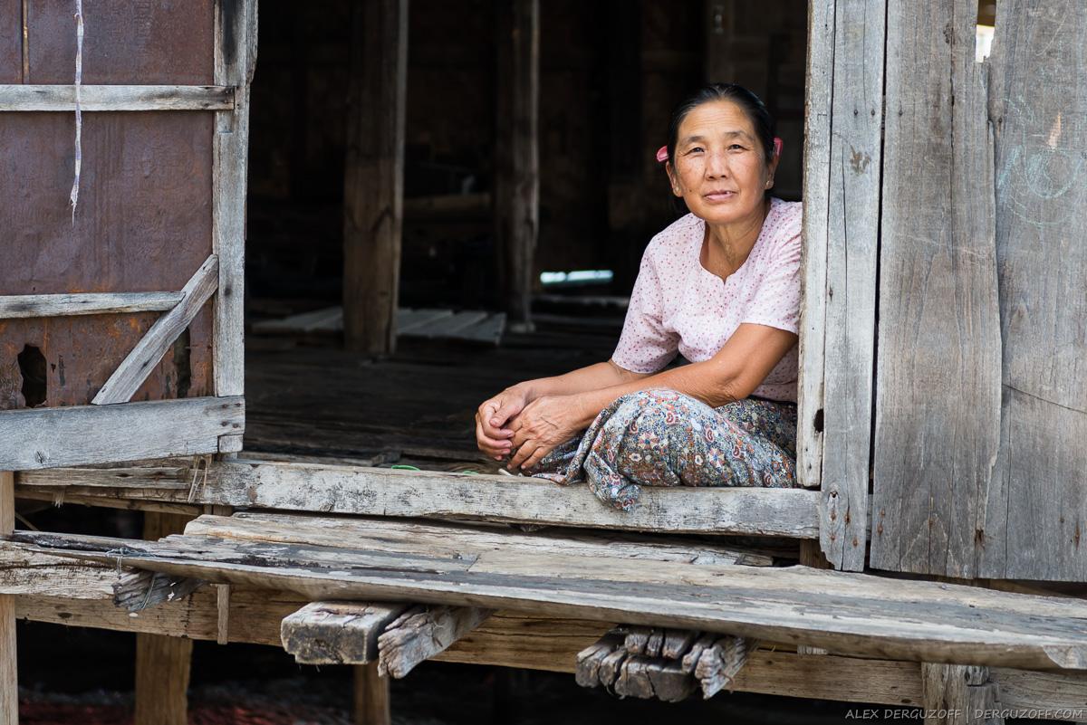 Пожилая женщина сидит на пороге своего дома