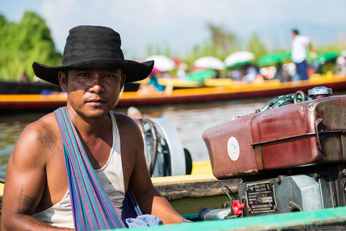 Бирманец в шляпе сидит в лодке