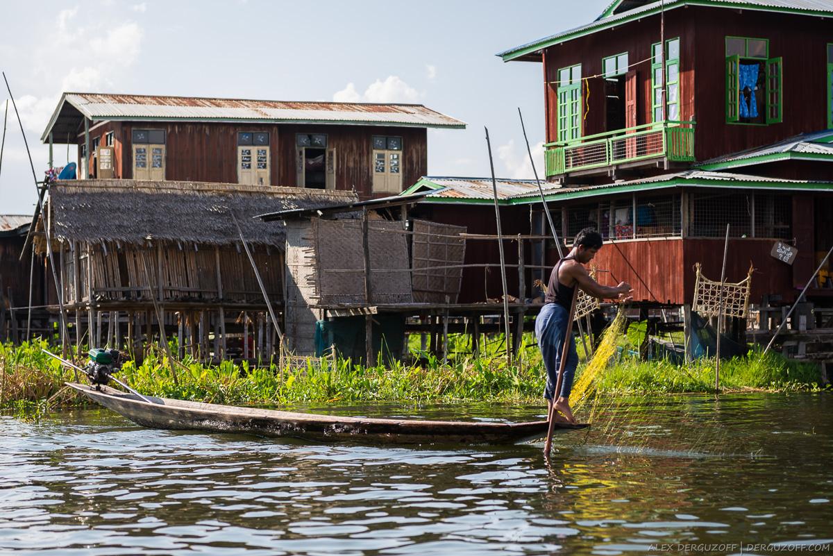 Мужчина закидывает сеть в воду возле своего дома