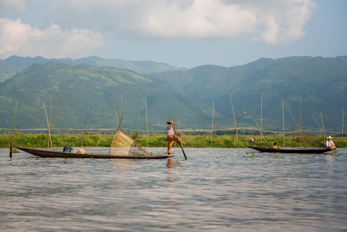 Рыбак с веслом стоит на лодке Мьянма