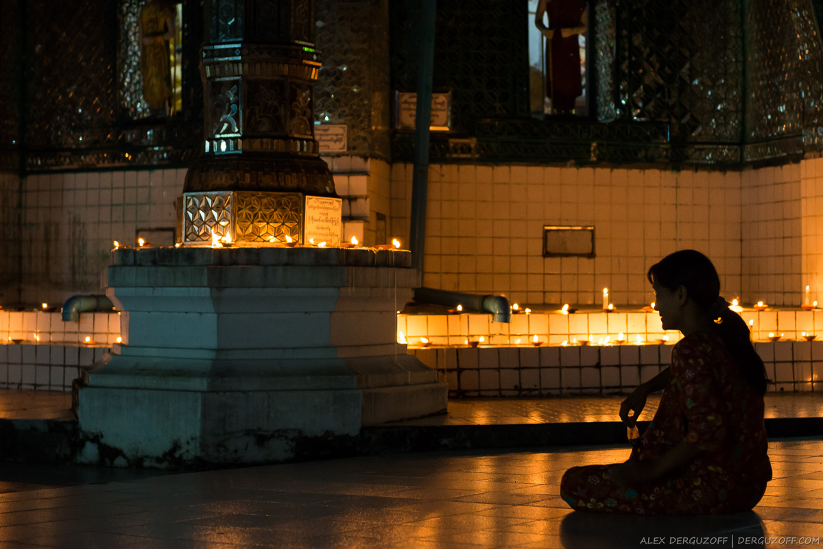 Женщина ночью в буддийском храме на фоне горящих свечей