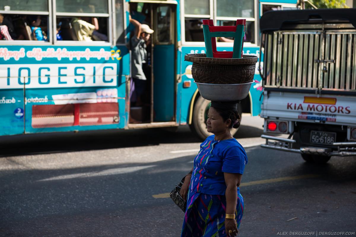 Женщина несёт на голове корзины и стул
