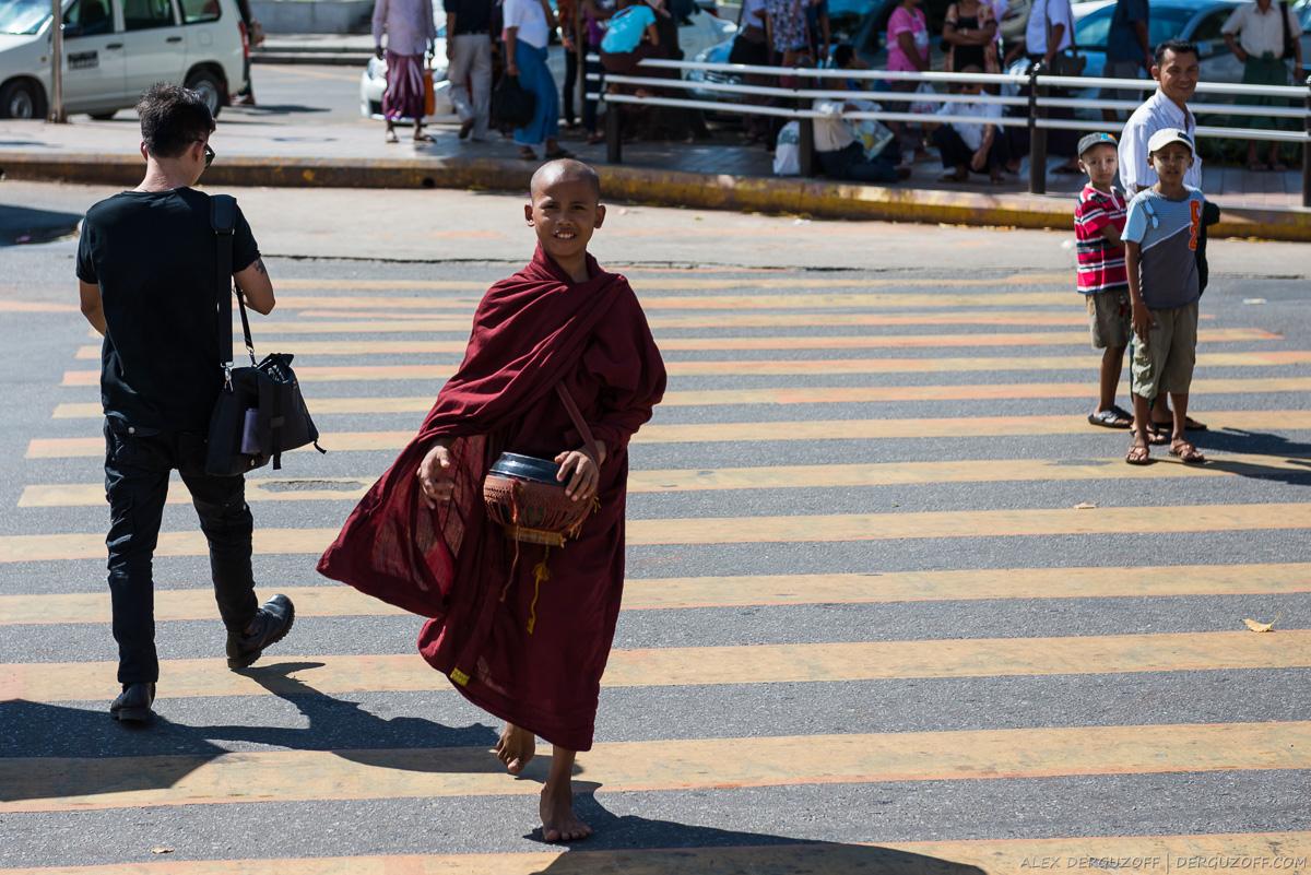 Молодой монах с чашей переходит дорогу