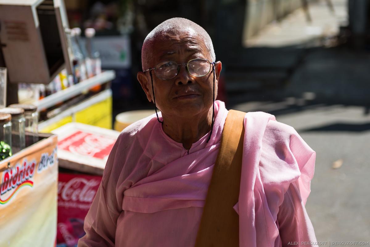 Пожилая монахиня в розовой одежде