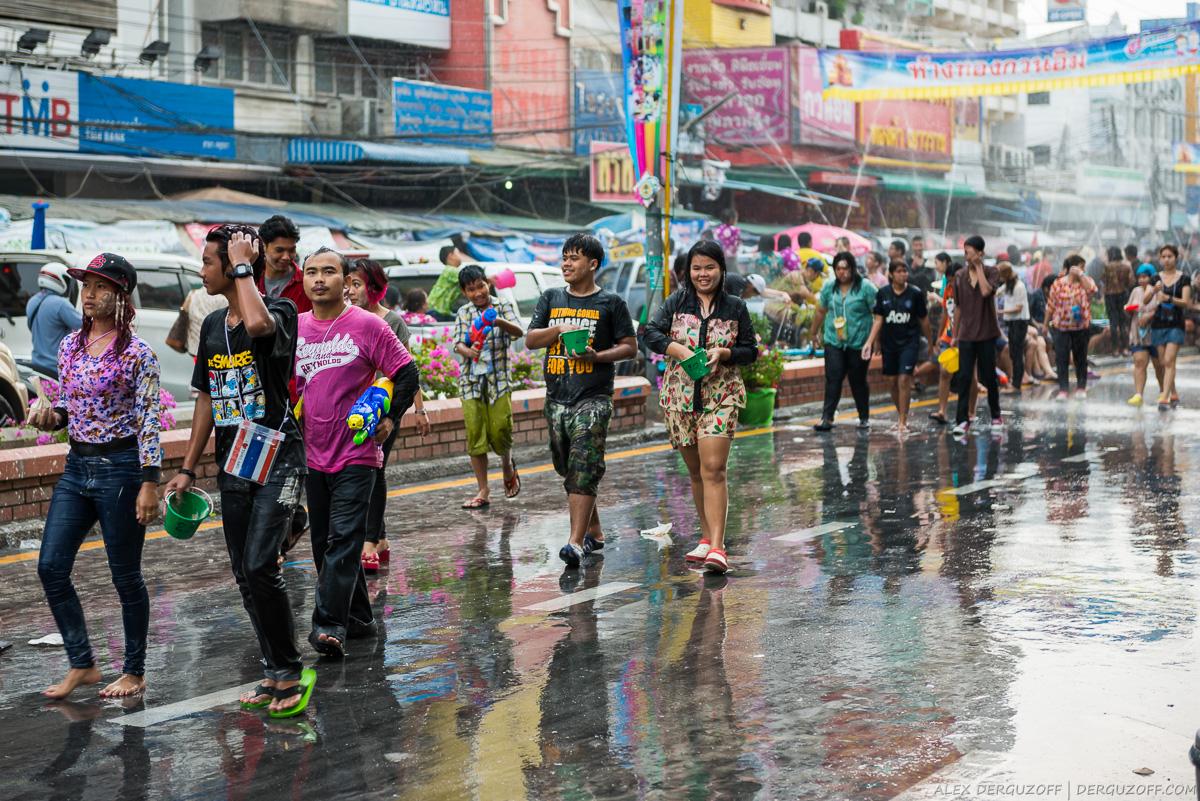 Тайцы идут по мокрой улице и мажут друг друга белой глиной
