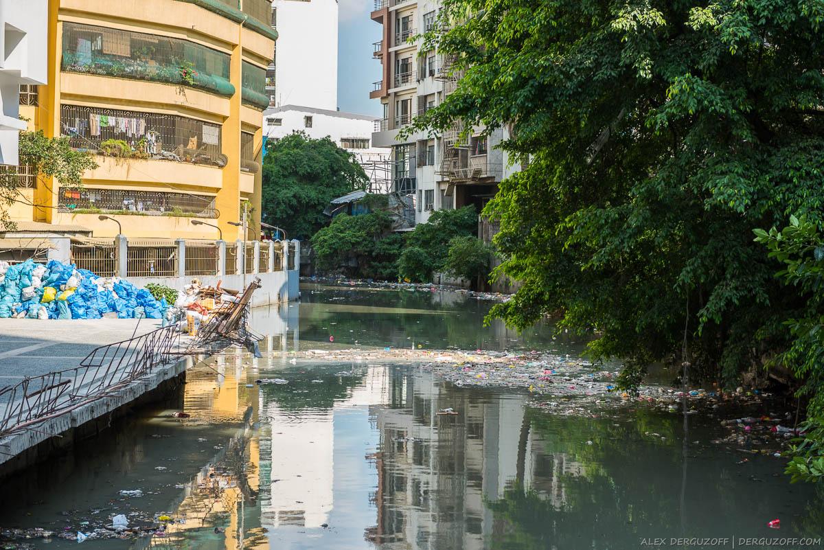 Мусор плывущий в мутном канале Манила Чайна-таун