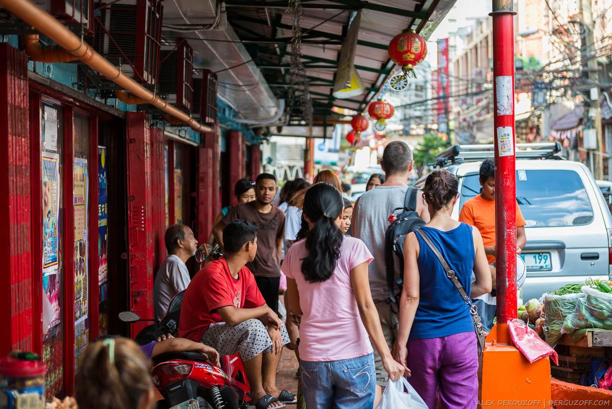 Прохожие на узкой улице Манила Чайна-таун