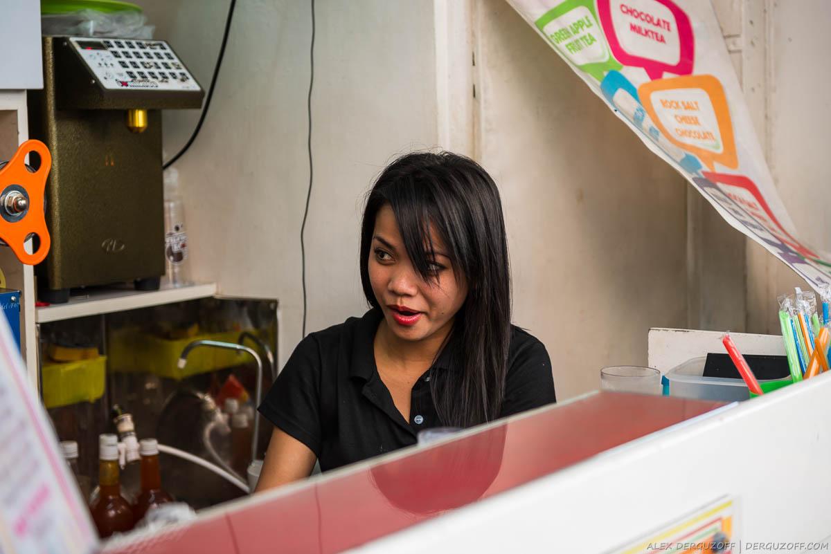 Девушка за прилавком магазина Манила