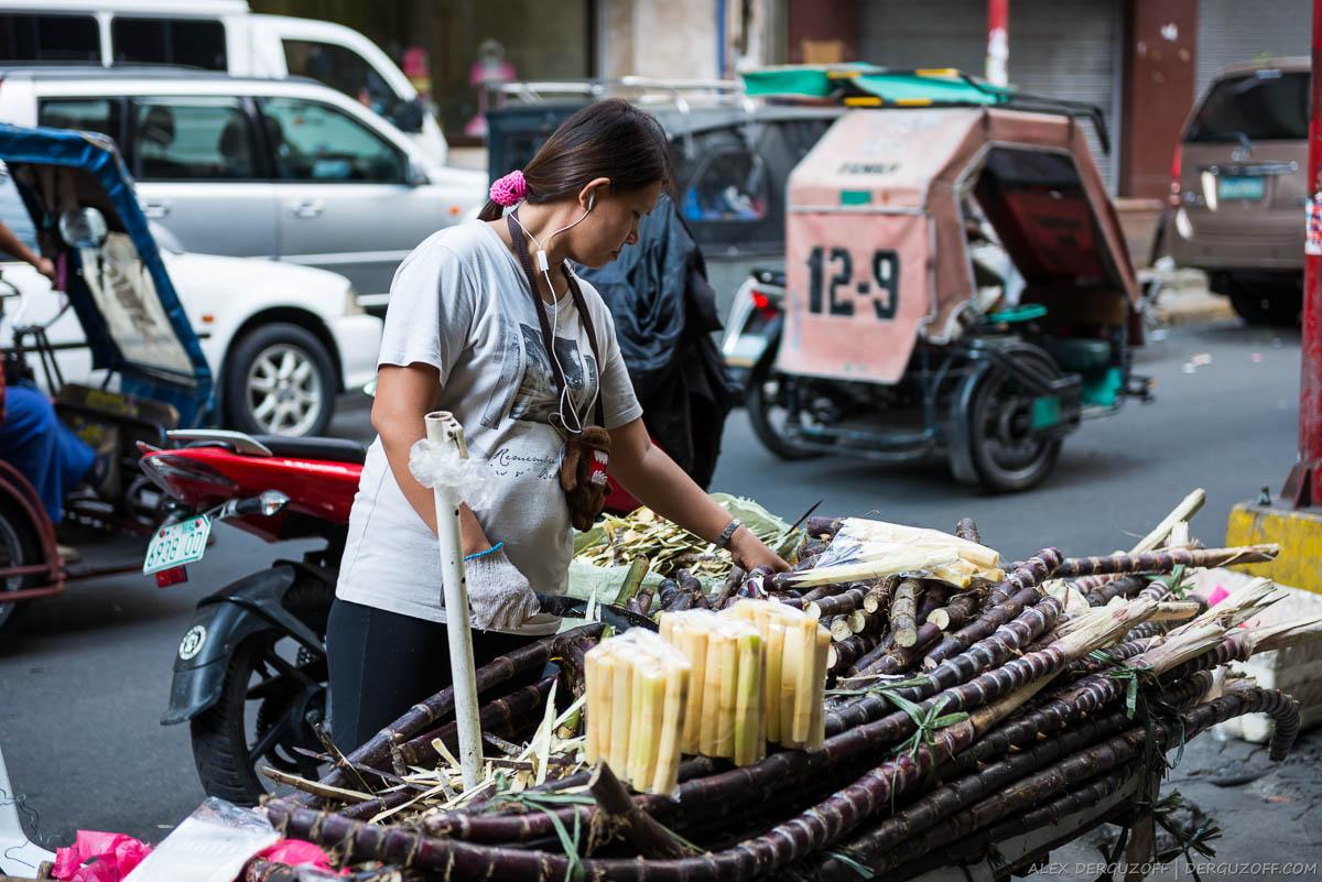 Девушка разрубает сахарный тростник на улице Манилы