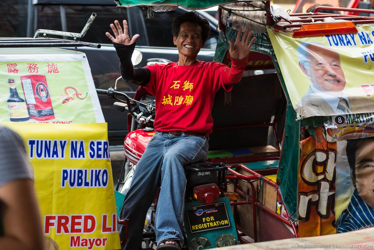 Мужчина в красной футболке с иероглифами машет руками