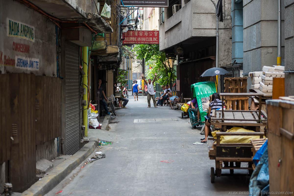 Зазывала машет руками в переулке Чайна-тауна
