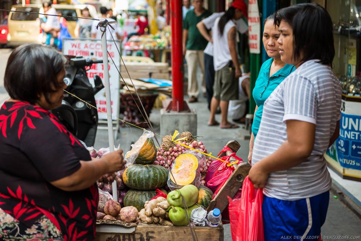 Женщины разговаривают с продавщицей фруктов на улице