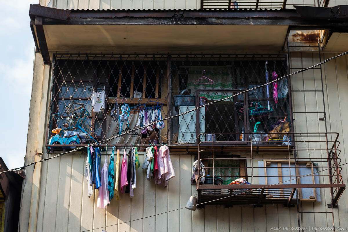 Ребенок сидит в окне за сушающимся бельем