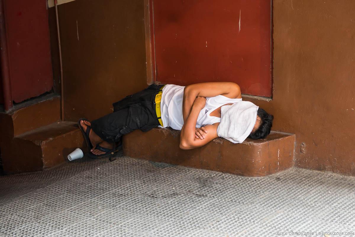Мужчина спит на земле накрывшись полотенцем