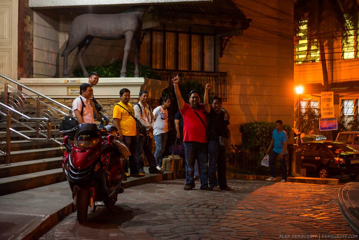 Филипиннские мужчины машут рукой на улице Интрамуроса