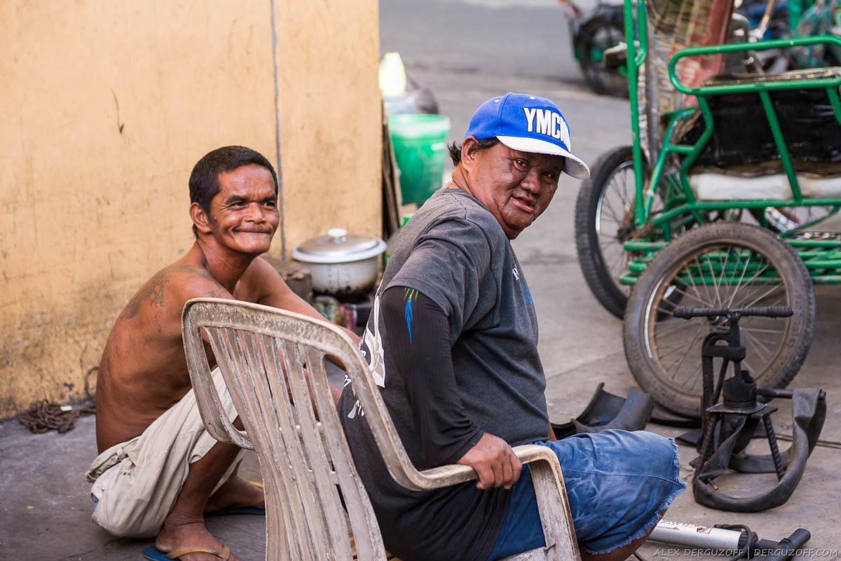 Толстый некрасивый филиппинец ремонтирует велосипед