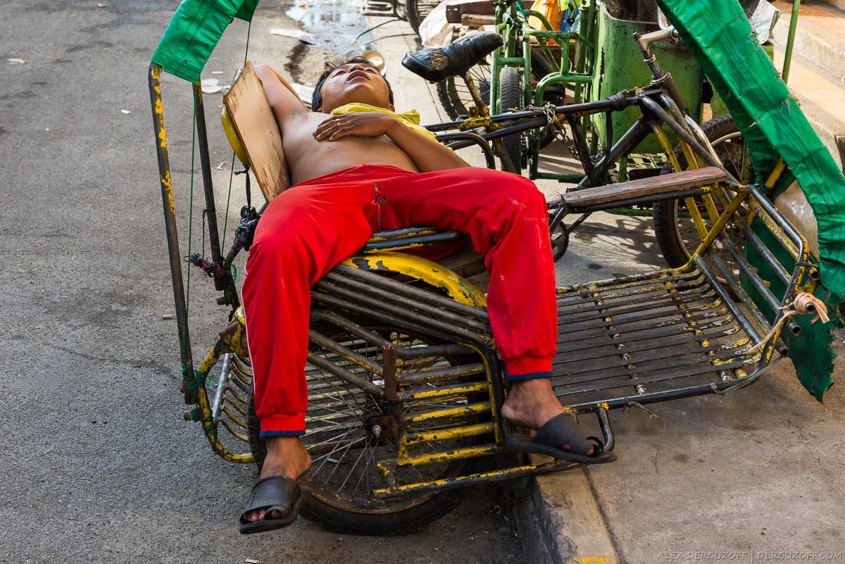 Водитель велосипедного такси спит в транспортном средстве