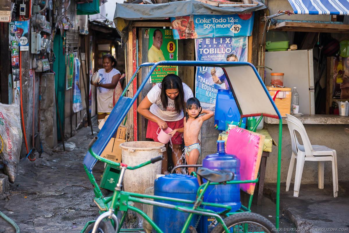 Женщина моет девочку на улице Манилы