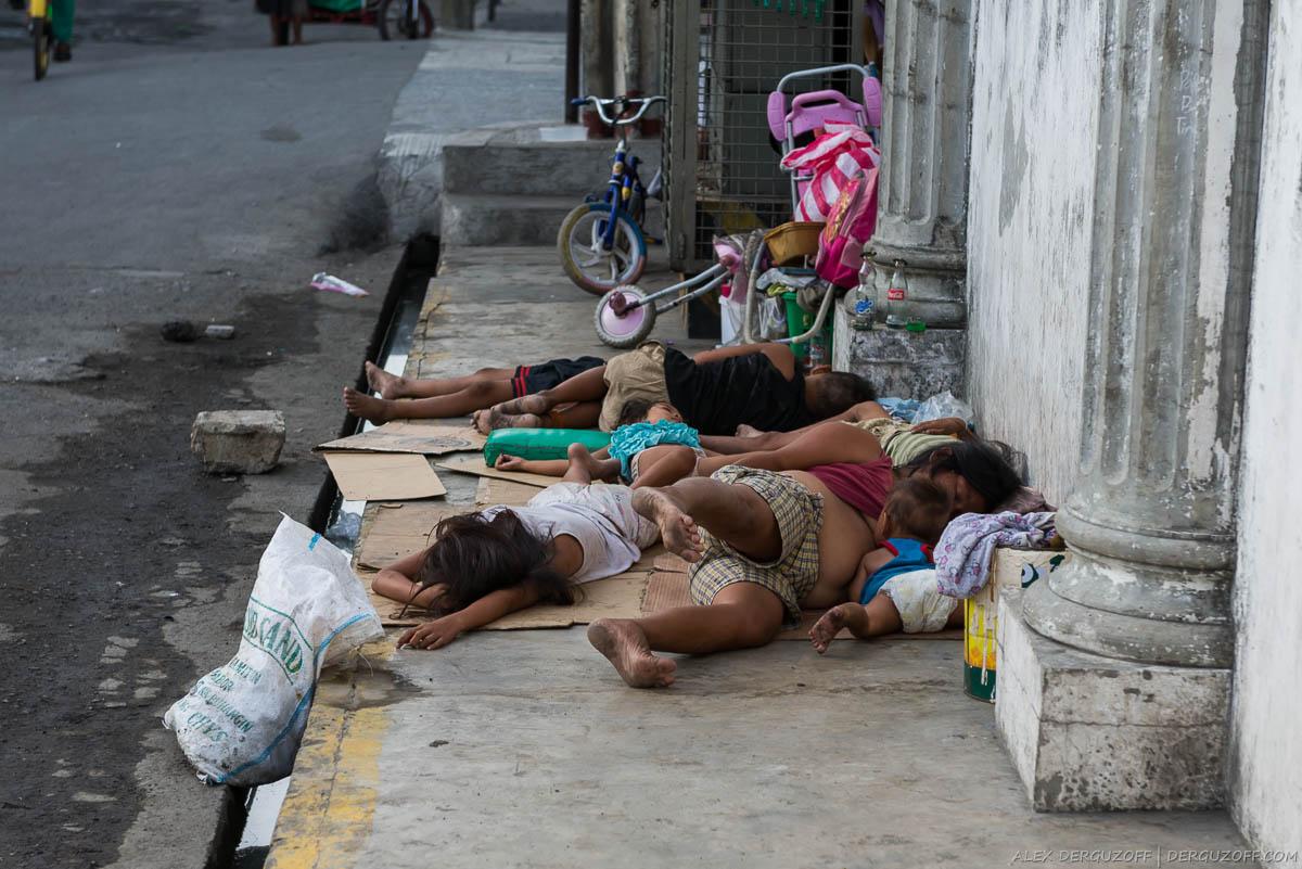 Семья нищих филиппинцев спит на дороге
