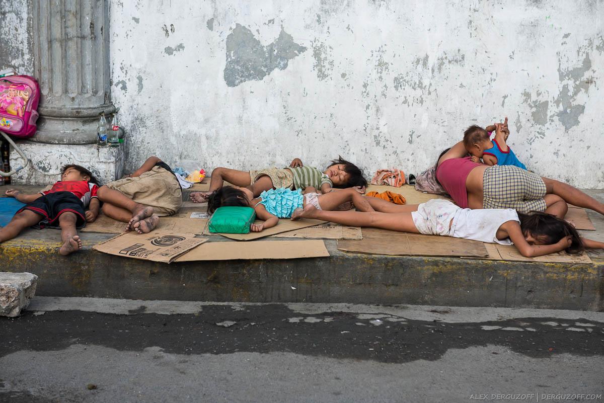 Грязные дети спят на тротуаре Манила Интрамурос