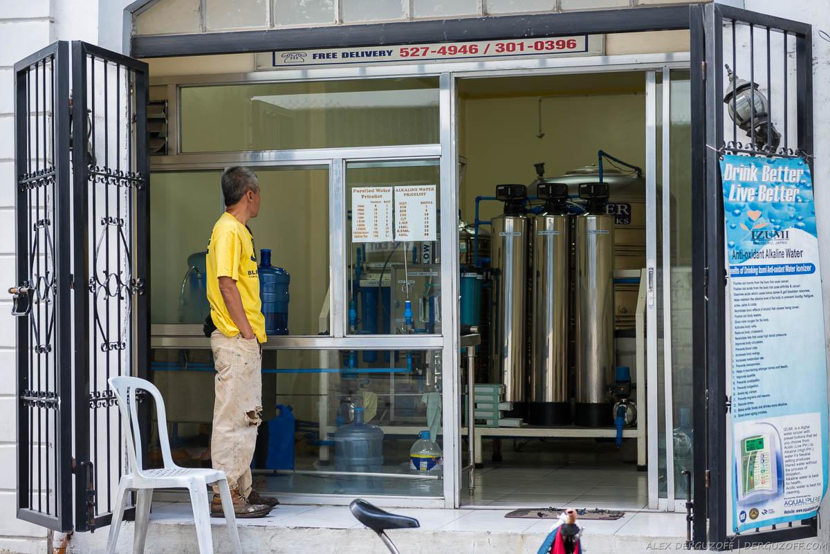 Мужчина стоит на пороге магазина по продаже питьевой воды