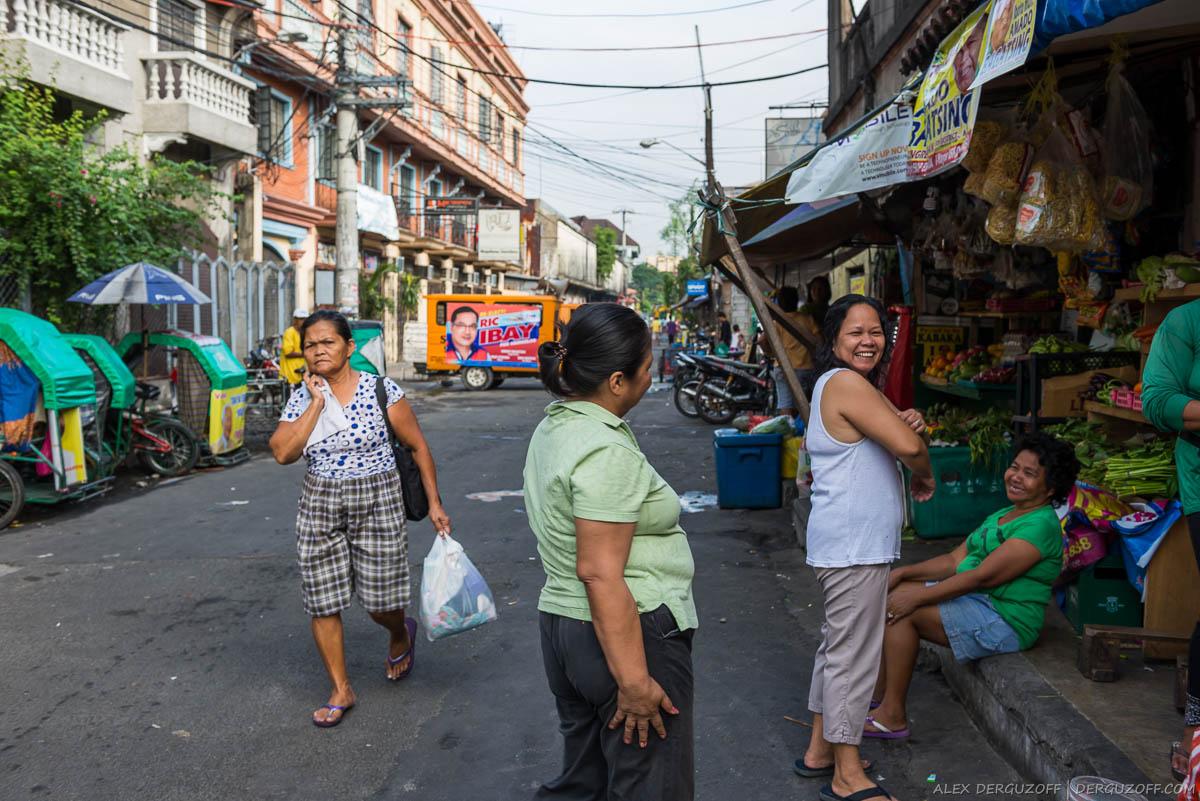 Женщины разговаривают на улице района Интрамурос Манила