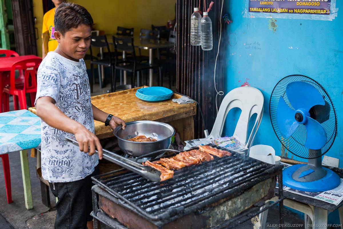 Мужчина жарит мясо на мангале Филиппины Манила