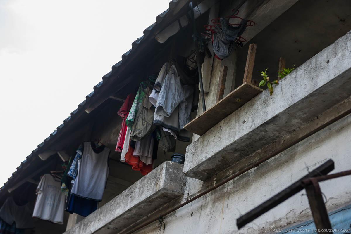 Белье на сушке под крышей здания Филиппины Манила