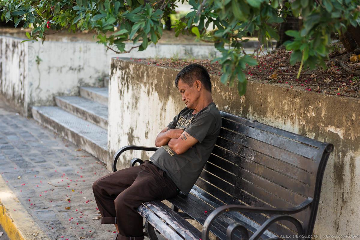 Филиппинец спит сидя на скамейке