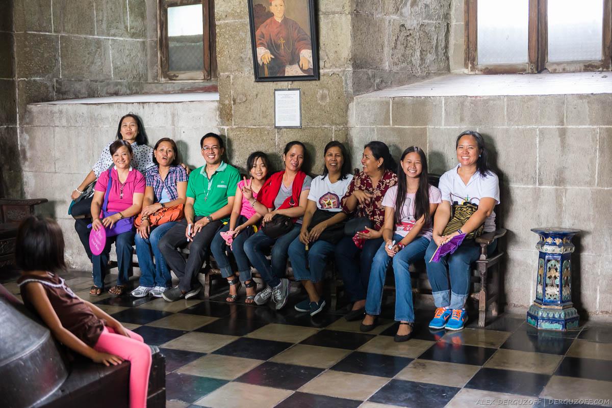 Филиппинцы-католики сидят на лавке в церкви