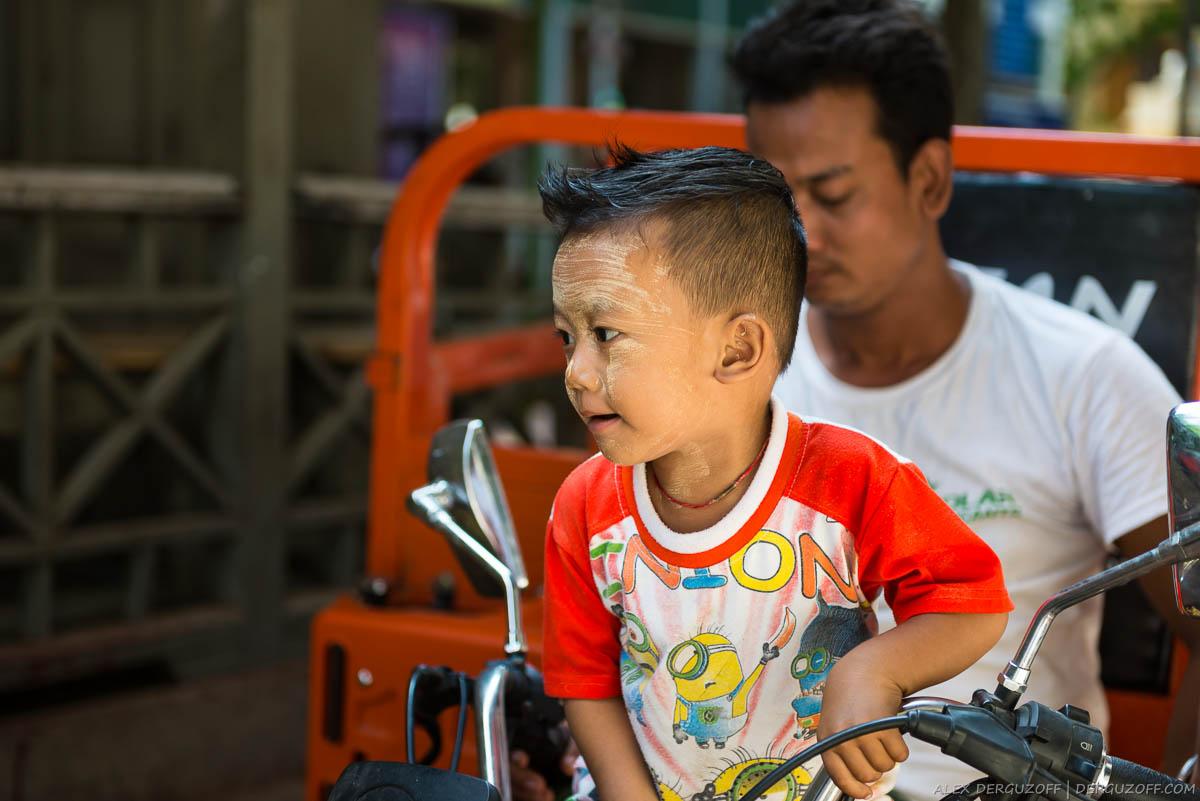 Ребенок в танаке сидит на мопеде Мьянма Мандалай