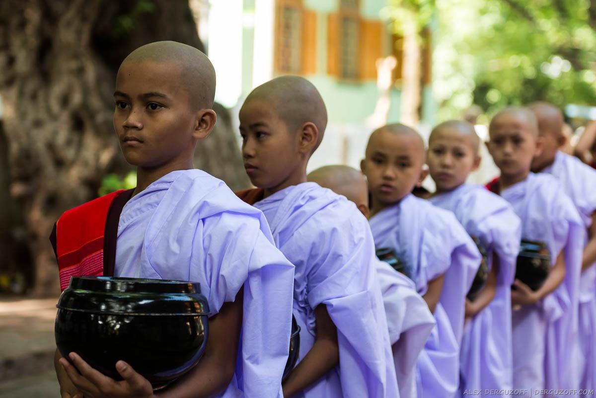 Молодые монахи с чашами стоят в очереди за едой