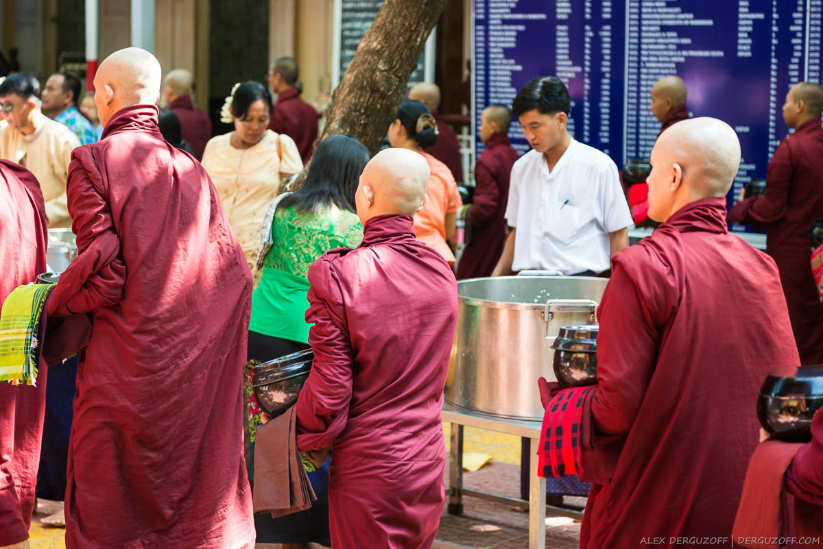 Местные жители участвуют в ритуале кормления монахов в Мандалае