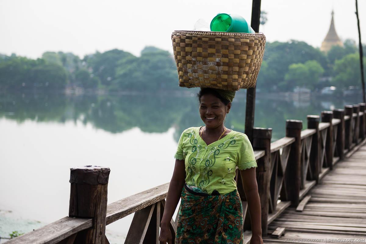 Бирманка с корзиной на голове идёт по мосту