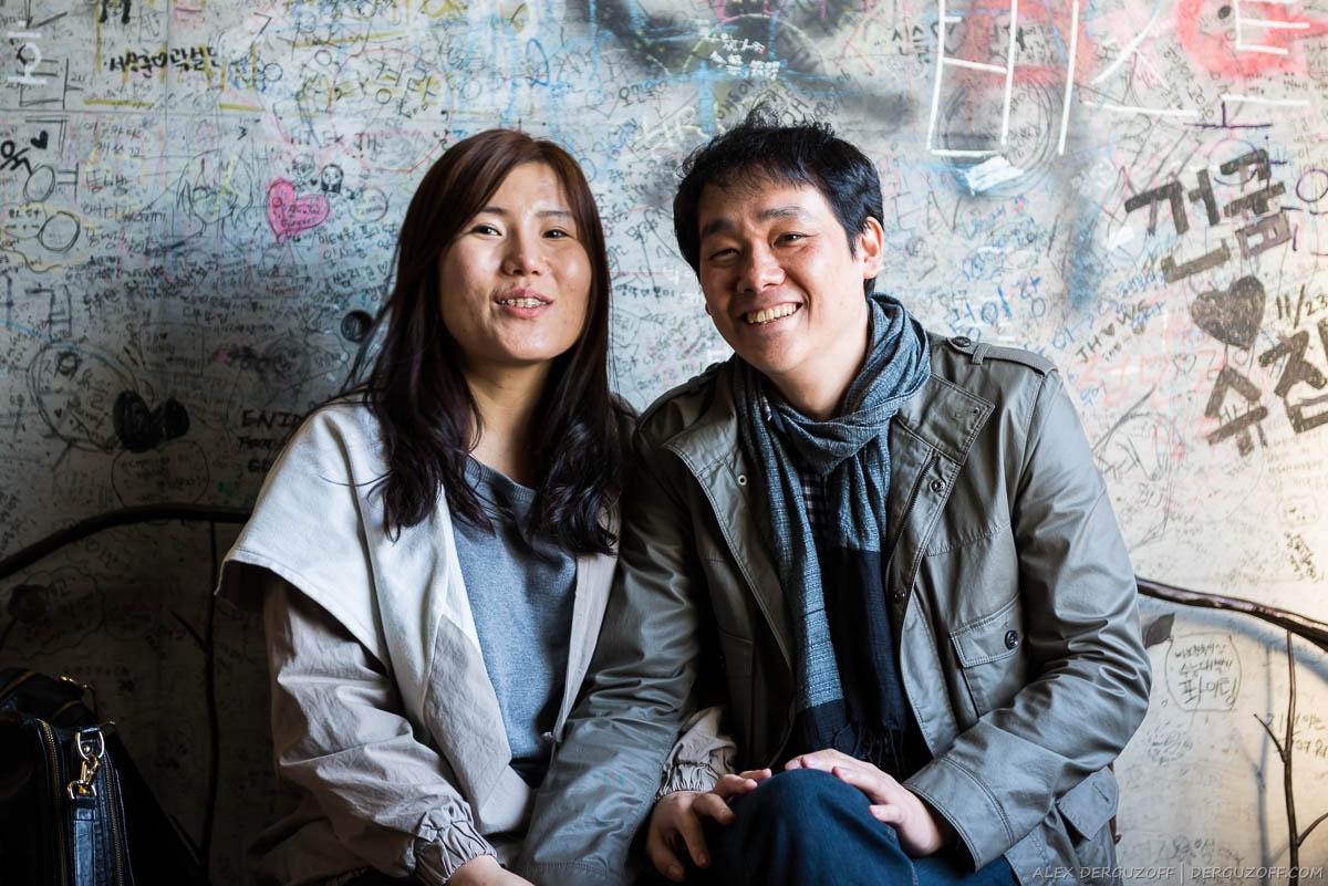 Молодая пара корейцев сидит на лавочке
