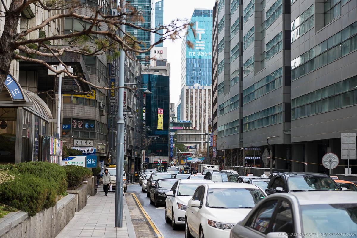 Пробка из машин на дороге между небоскребами