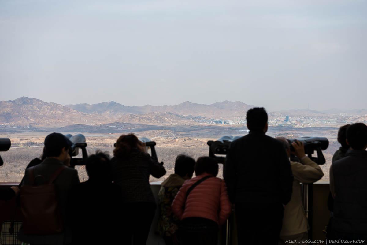 Люди смотрят на приграничные города Северной Кореи
