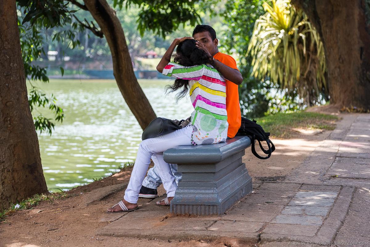 Молодая пара шри-ланкийцев сидит на лавочке на берегу пруда