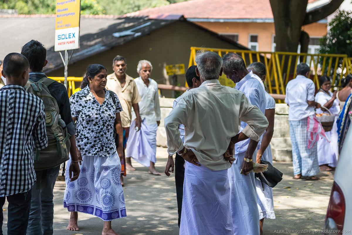 Мужчины в белых юбках на улице города Канди