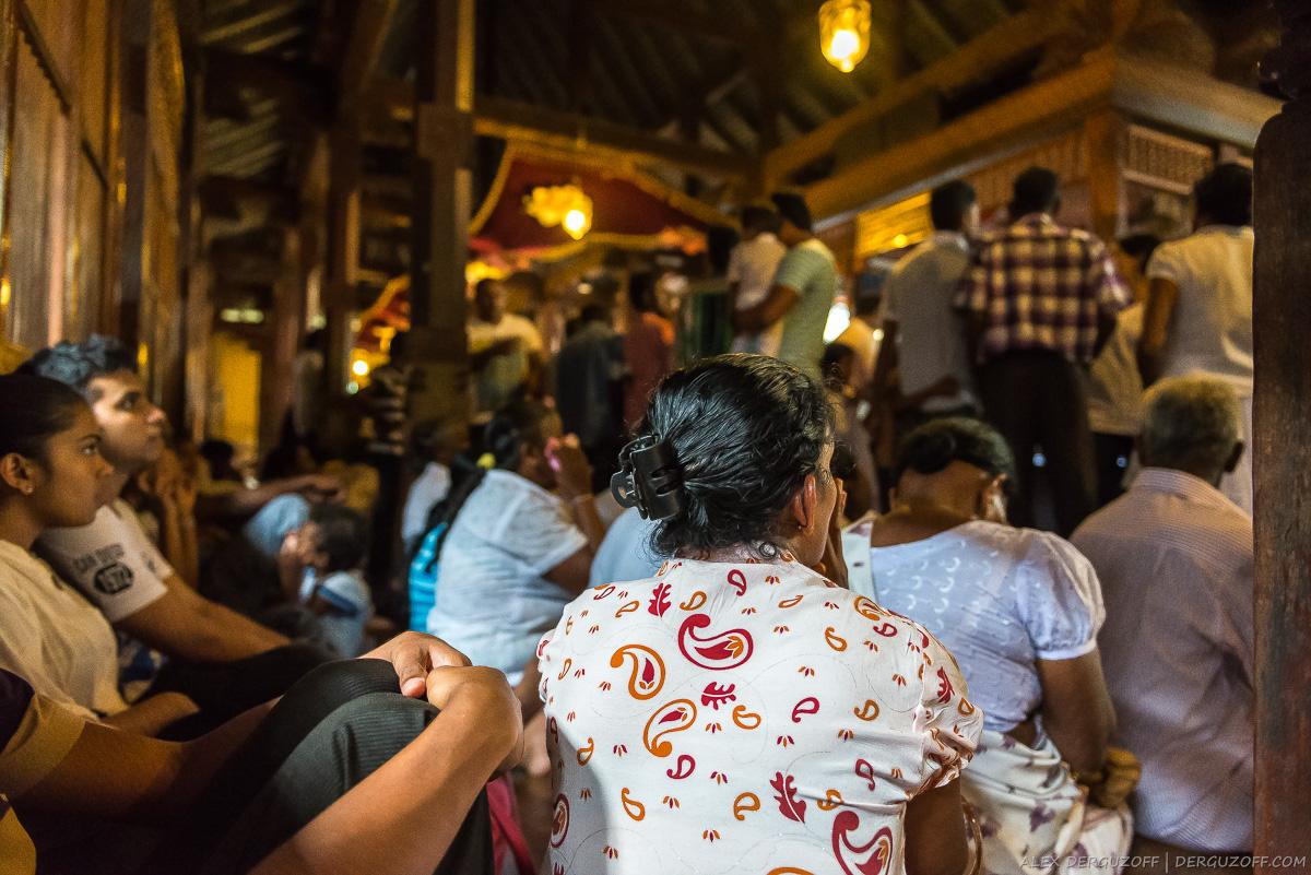 Поломники сидят на полу храма Шри-Ланка