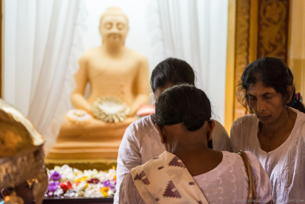 Женщины делают подношения статуи Будды
