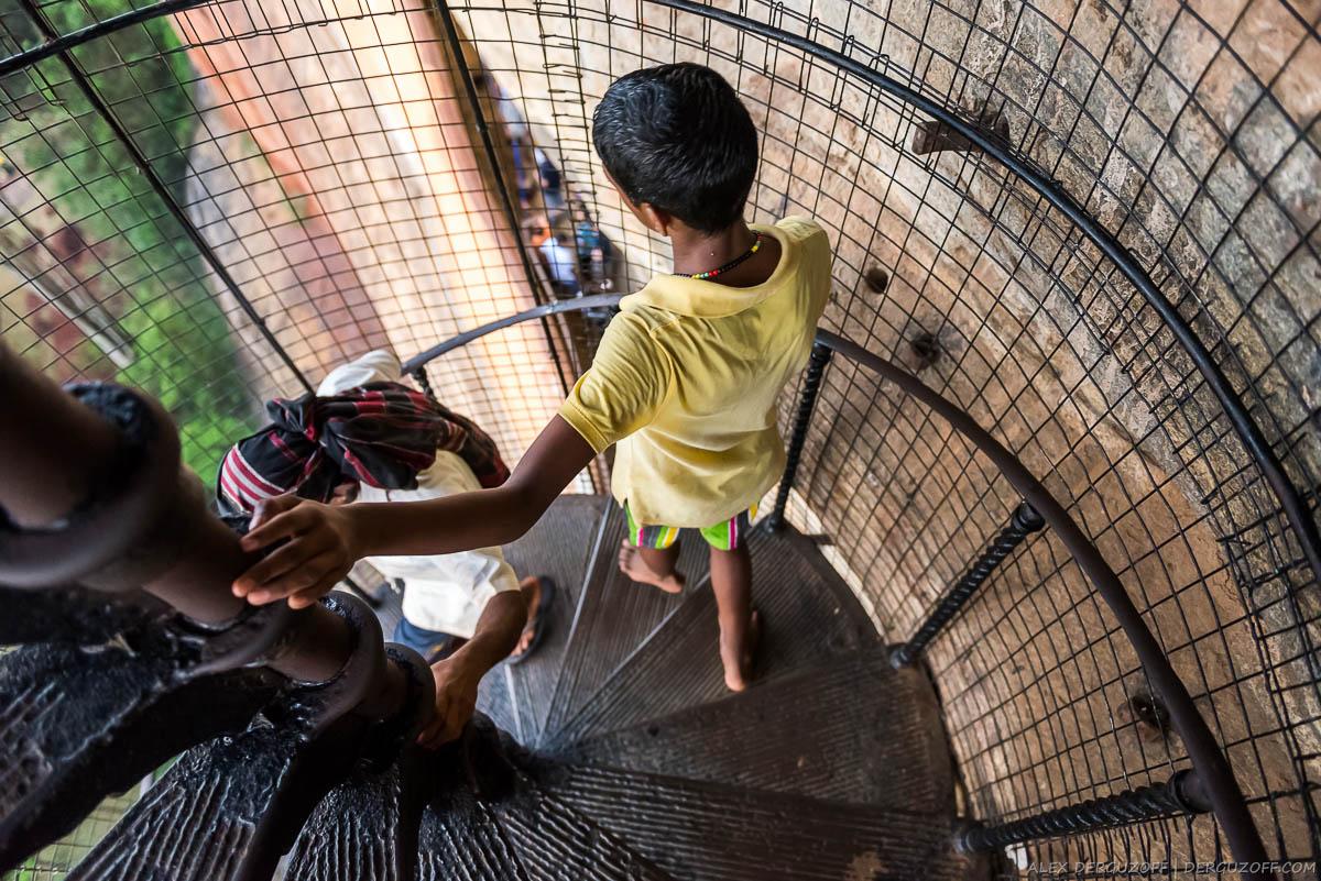 Ланкийский мальчик поднимается по винтовой лестнице на Сигирию