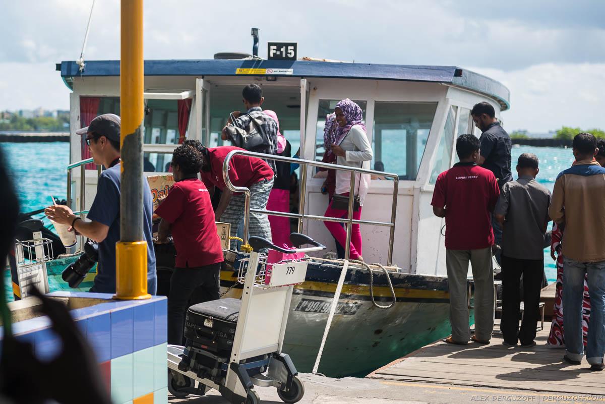 Мальдивцы садятся в лодку курсирующую между аэропортом и городом Мале