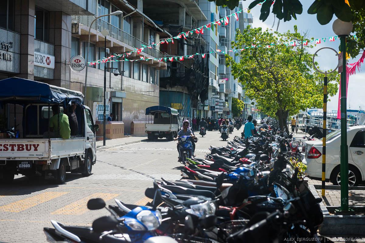Припаркованные мопеды на улице города Мале