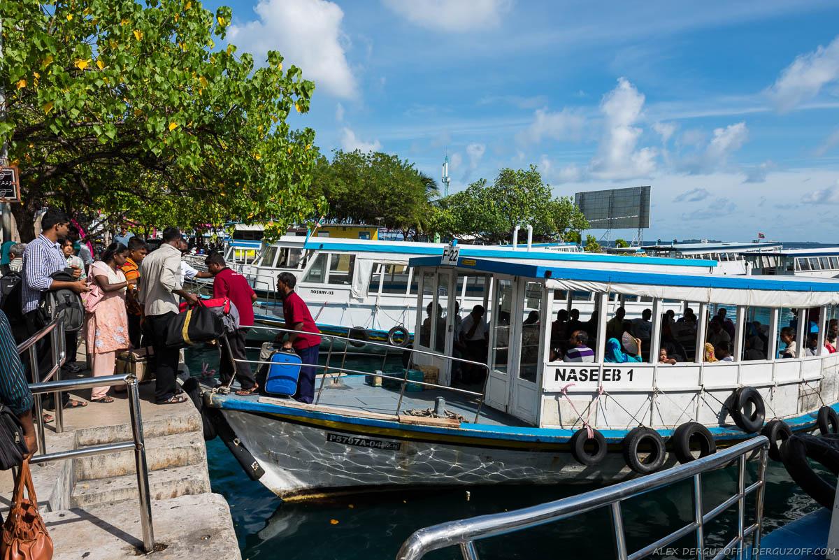 Люди ждут в очереди на посадку в транспортную лодку Мальдивы