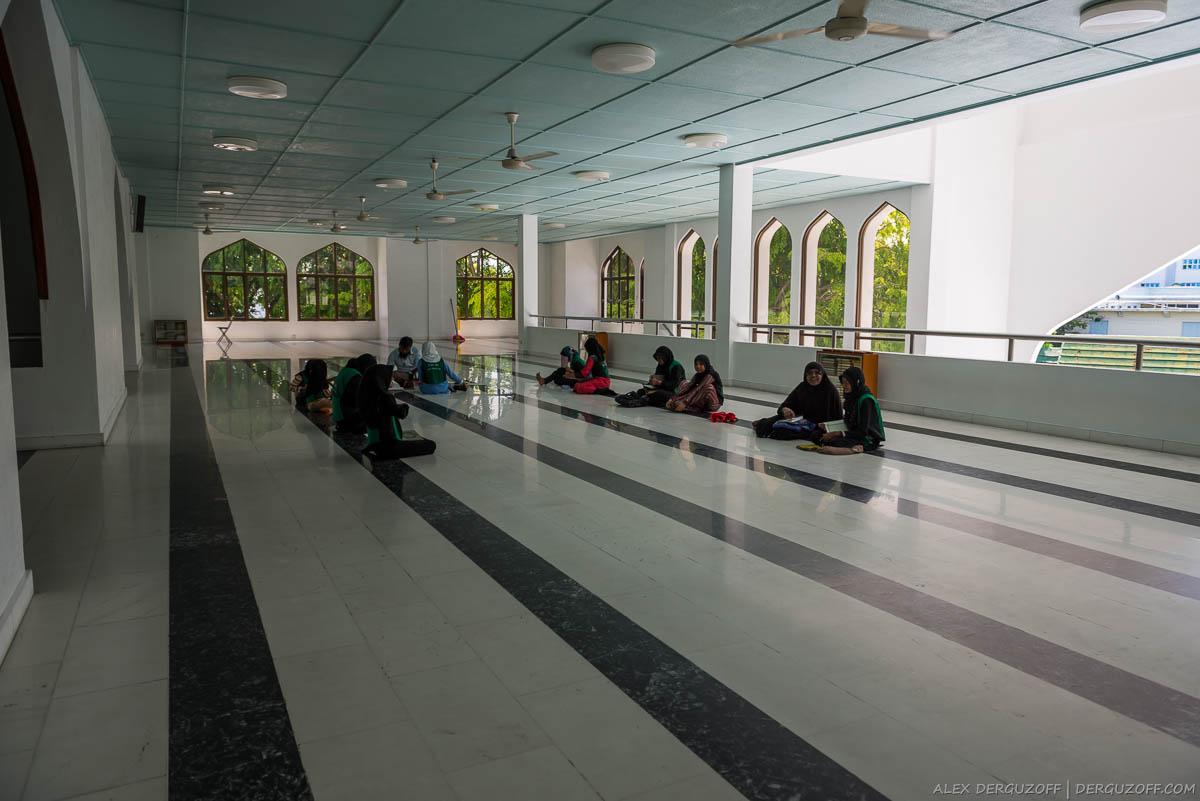 Девочки в хиджабах учатся сидя на полу в мечети