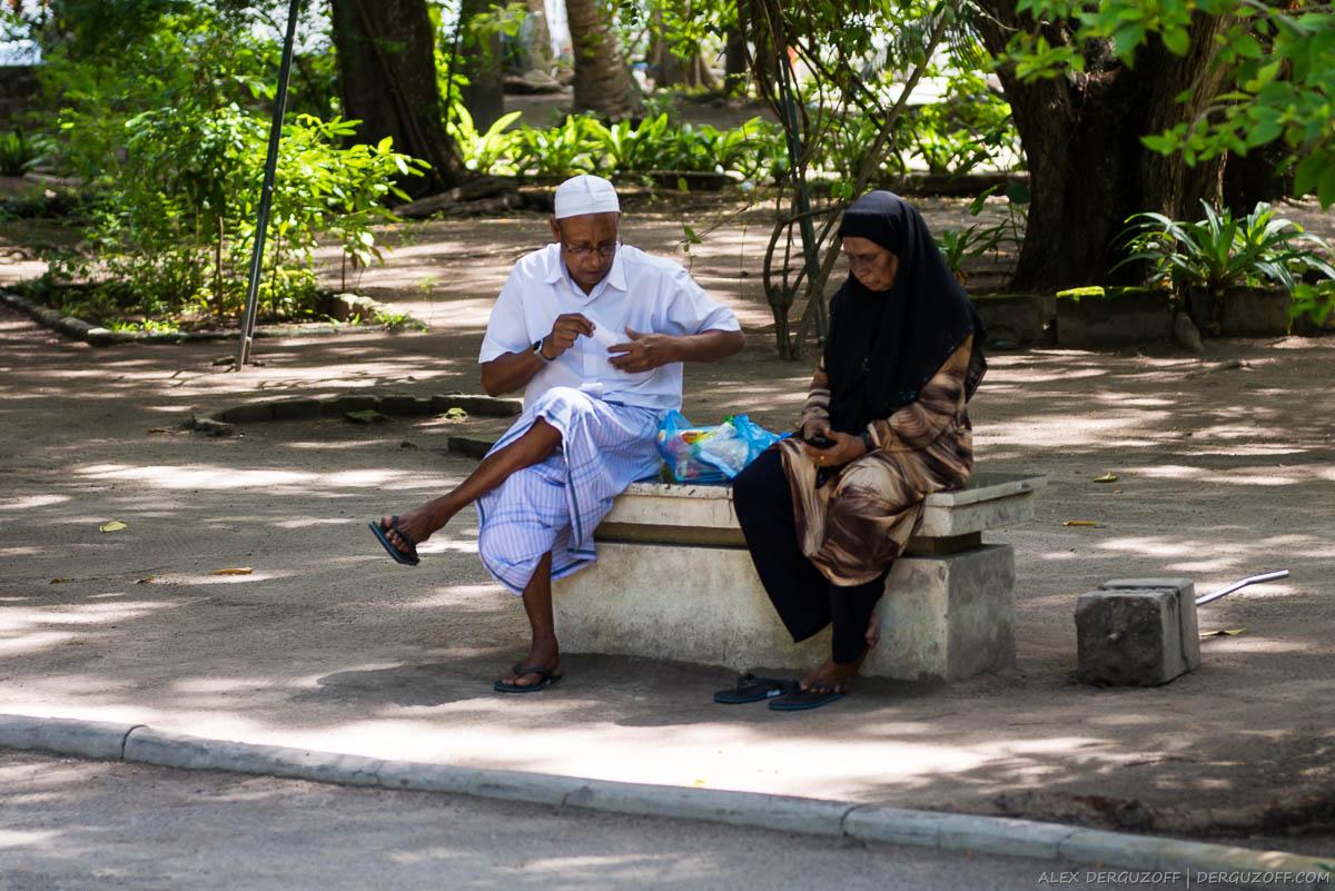 Мужчина в юбке и исламской шапочке и женщина в хиджабе сидят на лавочке